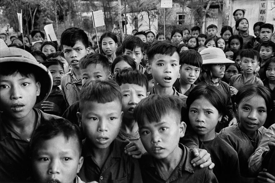 Vietnam, 1969. In a isolated village in North Vietnam, these schoolchildren stare at me as they leave the classroom, their curiosity mixed with alarm - I was probably the first Europeans they had ever seen.