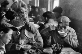 China, 1957. An engineer at the Anshan steel work eats in the cafeteria, her protective goggles clipped to the brim of her cap.