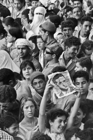 A woman brandishes the portrait of Ben Bella, Tlemcen, July 1962