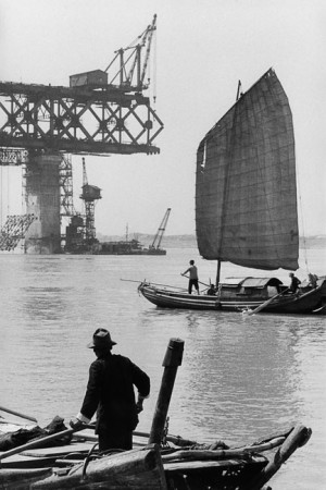 Junk in front of the construction site of a bridge over Yang-tseu-kiang, Wuhan, 1957
