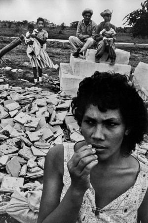 A family standing on the ruins on their home, destroyed by a hurricane, in Rio Cauto village, East of the island. 1963