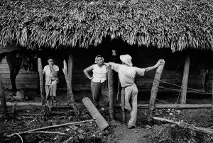 Inhabitants of Guamo village in front ont their homes, damaged by a hurricane, 1963