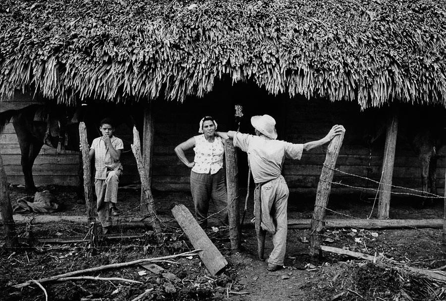 Habitants du village de Guamo devant leurs maisons, abîmées par le passage d'un ouragan, 1963