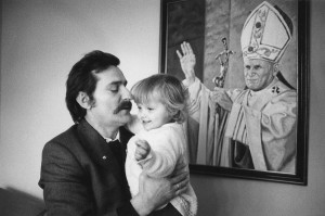 Lech Walesa and one of his children, in front of a portrait of pope Jean-Paul II, Poland, 1980