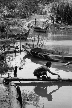 Angkor, Cambodia, 1990. A womman wasjes her sarong on the banks of the Stung Siem Reap river.