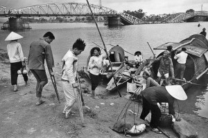 Two men who lost a leg during the long battle which destroyed a great part of Hué city, are waiting to cross the river on a boat, April 1968