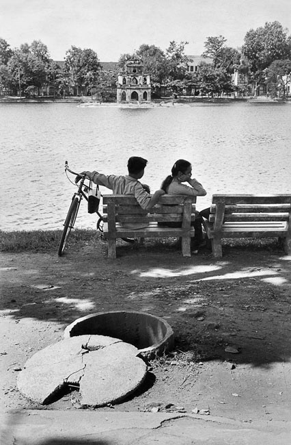 Couple along the lake in Hanoi, a shelter in the foreground, 1969