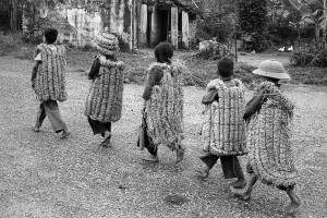 Children going to school wearing straw 'armors' supposed to protect them fro bomb fragments. North Vietnam, 1969