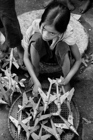 Girl selling toy airplanes, replicas of the MIGs used by the Northern army, Hanoi, 1969